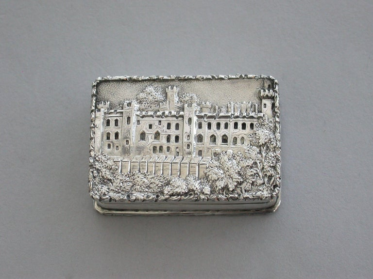 A very fine early Victorian silver 'Castle Top' Vinaigrette, of rectangular form with engine turned decoration to the base and reeded sides, raised foliate borders, the lid depicting a view of Warwick Castle in high relief, silver gilt interior with