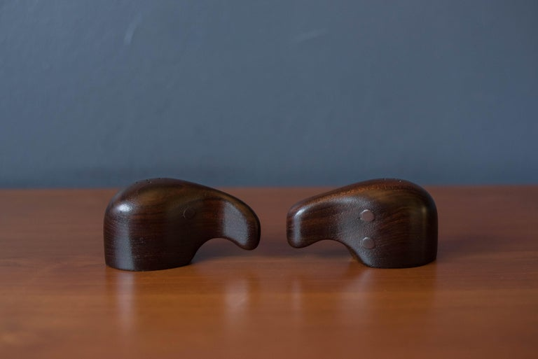 Mid-Century Modern abstract salt and pepper shakers designed by Don Shoemaker for Señal, S.A. Mexico. This set is handmade in rosewood with unique brass ring dispensers that makes for a standout tabletop setting. Each shaker is numbered and