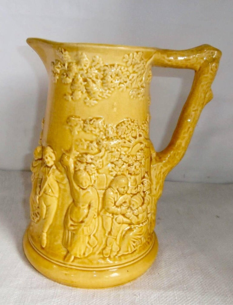 Early large rustic yellow Majolica pitcher with a tavern scene signed Sarreguemines, circa 1870.