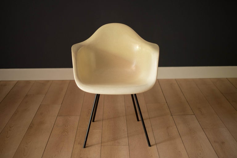 Iconic design (DAX) dining armchair x-base by Ray and Charles Eames, circa early 1950's. This second generation parchment colored armchair retains a high gloss finish supported by the original black X steel base with large shock mounts. An earlier