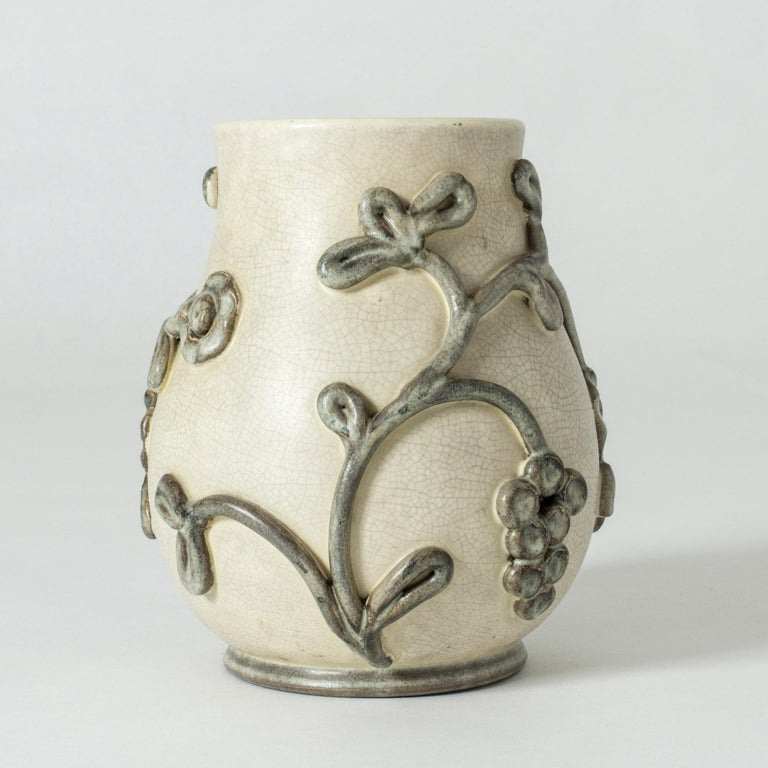 Beautiful earthenware vase by Eva Jancke-Björk. Muted natural tones in off-white and grey. Decor of a stylized grape vine with thick glaze.