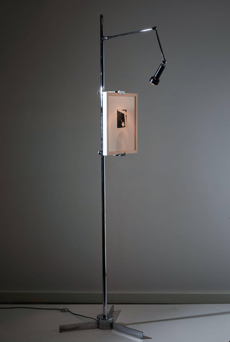Easel floor light by Angelo Lelli for Arredoluce. Designed and manufactured in Italy, circa 1960s. Chrome plated brass, pivoting enameled metal shade, with adjustable arms for displaying artwork and tripod base. Original cord. On/off step switch.
