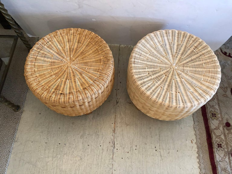 Great looking pair of woven rattan and wicker round ottomans having 4 tapered light wood legs. Perfect for a stylish beach house. One ottoman is slightly darker than the other.