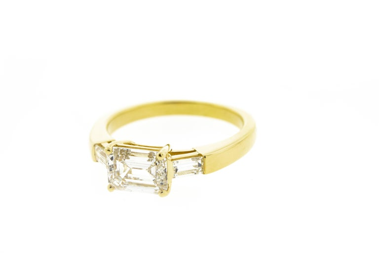 This three stone emerald cut diamond engagement ring is set in yellow gold. It features three emerald cut diamonds in an east-west orientation rather than the normal north south. It's a refreshing twist on a timeless classic. This ring can be
