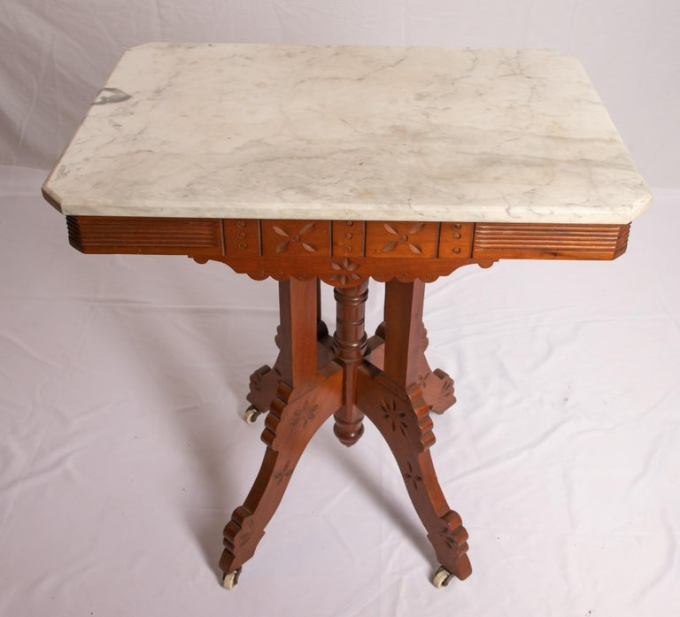 Offering this stunning Eastlake marble-top parlor table. Starting at the bottom on four legs that come to the center having some light floral carving. Rises from there on a center spindle that has four rectangle post around it. The skirt of the