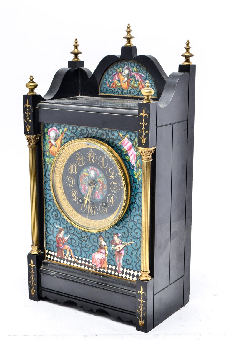 Eastlake movement mantel clock in black marble and enamel. The piece has an enamel front depicting an artist, model and musician lute player. Decorative brass finials and Corinthian columns on the sides. Made in the 19th century. In great antique