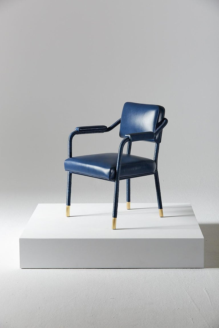 The Easton dining chair is uniquely crafted from stainless steel and Italian leather. Hand-wrapped leather cloaks a tubular frame ending with brass accent feet. Saddle-stitched leather forms the seat and additional leather pads bring extra comfort