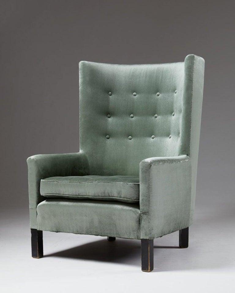 Upholstered in velvet and feet in black lacquered wood.