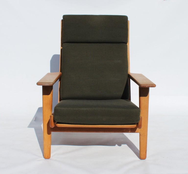 Easy chair with tall back, model GE290A, designed by Hans J. Wegner and manufactured by GETAMA in the 1960s. The chair is of soap treated oak and upholstered with dark green Hallingdal wool.