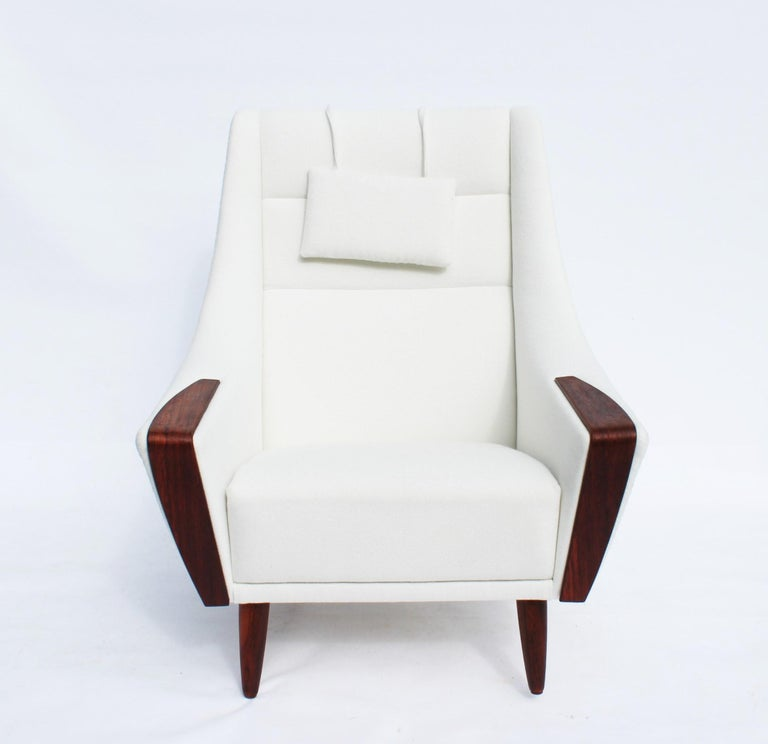 Easy chair with tall back upholstered in white fabric and with rosewood of Danish design from the 1960s. The chair is newly upholstered and in very good condition.