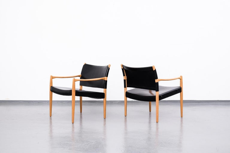 Pair of black leather easy chairs with oak frame. Model