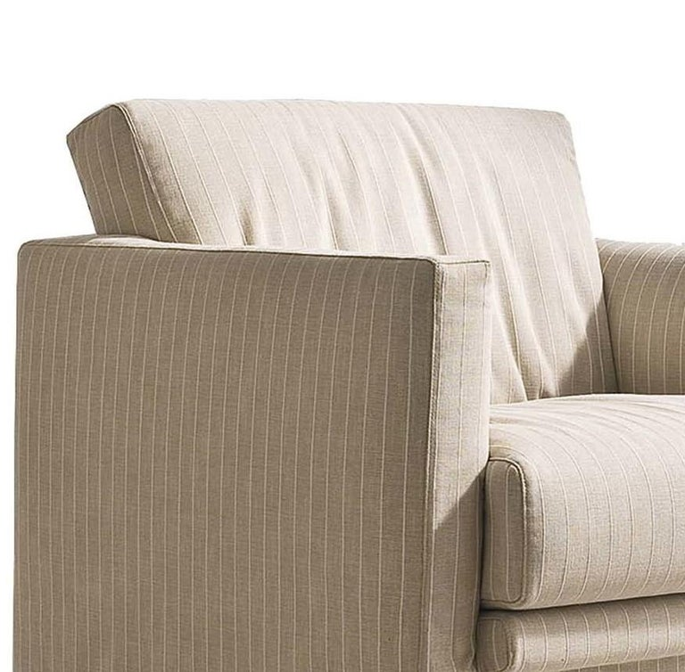 Simple yet refined, the classic Silhouette of this comfortable armchair features a polyurethane padding with wide seat, tilted back and generous track armrests. Upholstered with a removable fabric cover in a soft ivory color (col. 1610-105 cat.