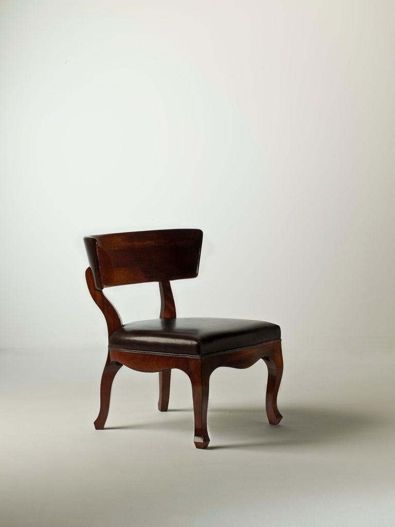Recalling Scandinavian design of the 1950s for its use of curved wood, and typical traits of Louis XV's furniture style for the inlaid decoration of the arms and feet, is the small armchair Easy XV by Studio R2d. The seat is characterized by the