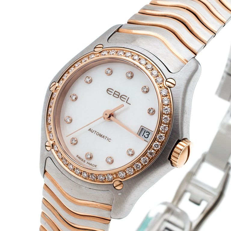 Classic and elegant, this Classic Wave wristwatch from Ebel is designed to complement your fashion taste with utmost subtlety. It has a stainless steel case with a diamond-encrusted, screw-detailed 18k rose gold bezel featuring a mother of pearl