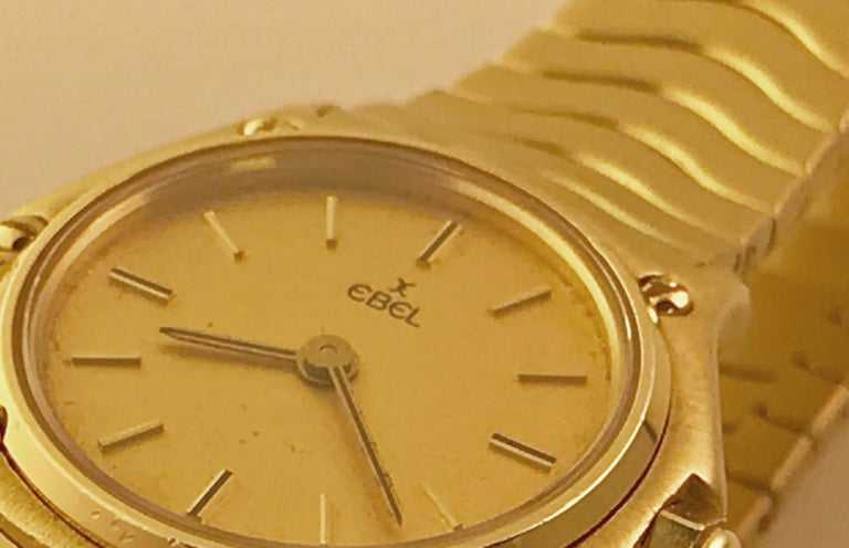 Ladies Ebel Sport Classic Mini in 18k gold. This watch features a Champagne dial and yellow gold hour markers. It is 23mm in case diameter. It also features a two-peice 18k gold bracelet with push button deployant clasp. This watch is in excellent