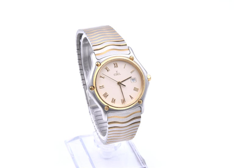 Movement: quartz Function: hours, minutes, seconds, date Case: 32mm stainless steel case, sapphire crystal, yellow gold smooth bezel, push/pull crown Band: Ebel two tone wave bracelet, deployment clasp Dial: cream dial, date at 3 o'clock, gold
