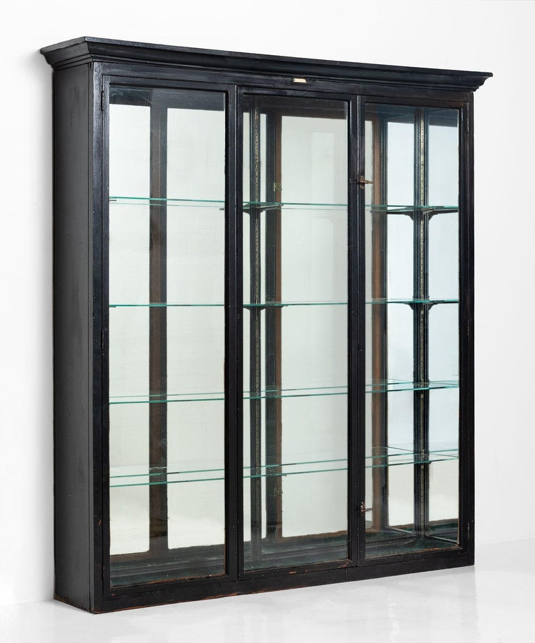 Ebonized display cabinet, England, circa 1920  Three-door shop fitting display with mirrored back and four glass shelves.