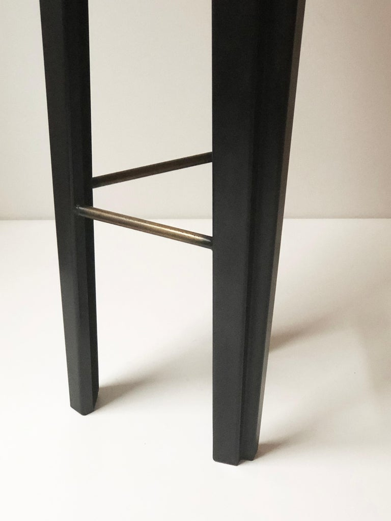 """Ebonized oak bar stool signed by Cal Summers Materials: Ebonized oak, blackened steel Steel insert with bronze finish Dimensions: 12 1/2""""D x 12 1/2""""W x 29""""H  Cal Summers is a British designer who makes bespoke handmade furniture and"""