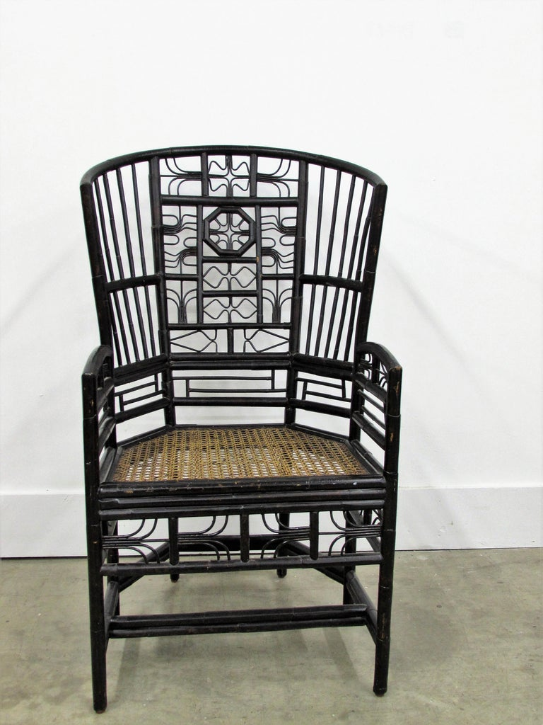 Vintage ebonized Brighton Pavilion highback Chinese Chippendale armchair rising on six legs this intricately crafted iconic armchair with original cane seat, features bamboo frames and Chinese themed bamboo open work inspired by Chippendale design.