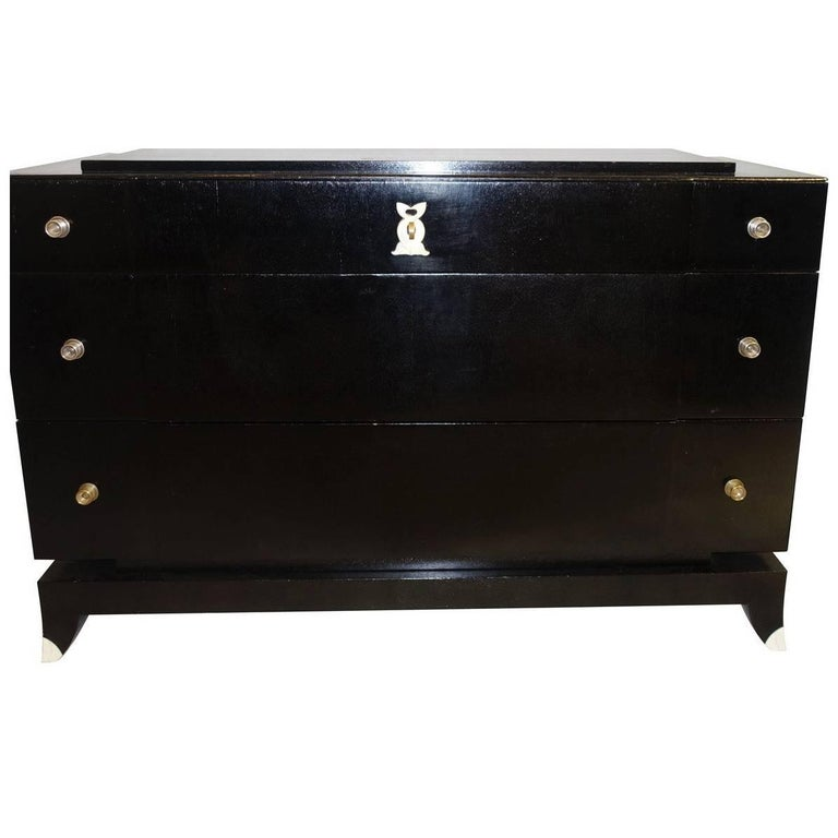 1930s French ebonized mahogany three drawer commode with tipped legs. Unusual raised top. Polished nickel pulls.