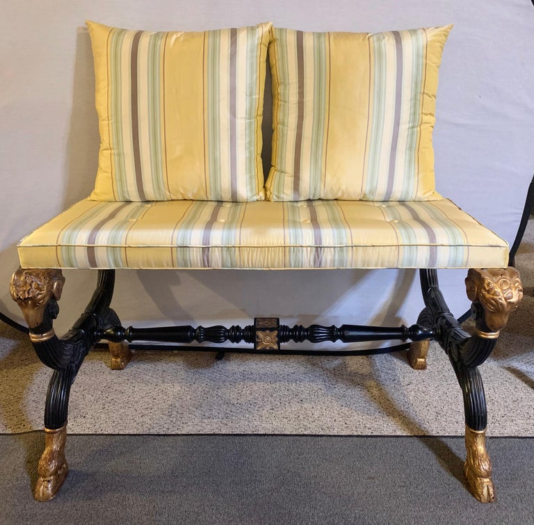 Ebonized & gilt benches or settes having mantra silk scalamandre upholstery. A fine pair each with a gilt rams head hand-rest. The pair of Hollywood Regency benches are simply stunning in their ebony finish with gilt carved hoof feet and rams heads