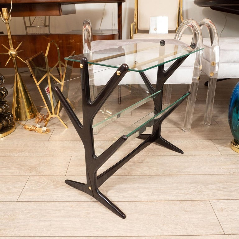 Angular, ebonized wood and glass side table with magazine holder and brass details.