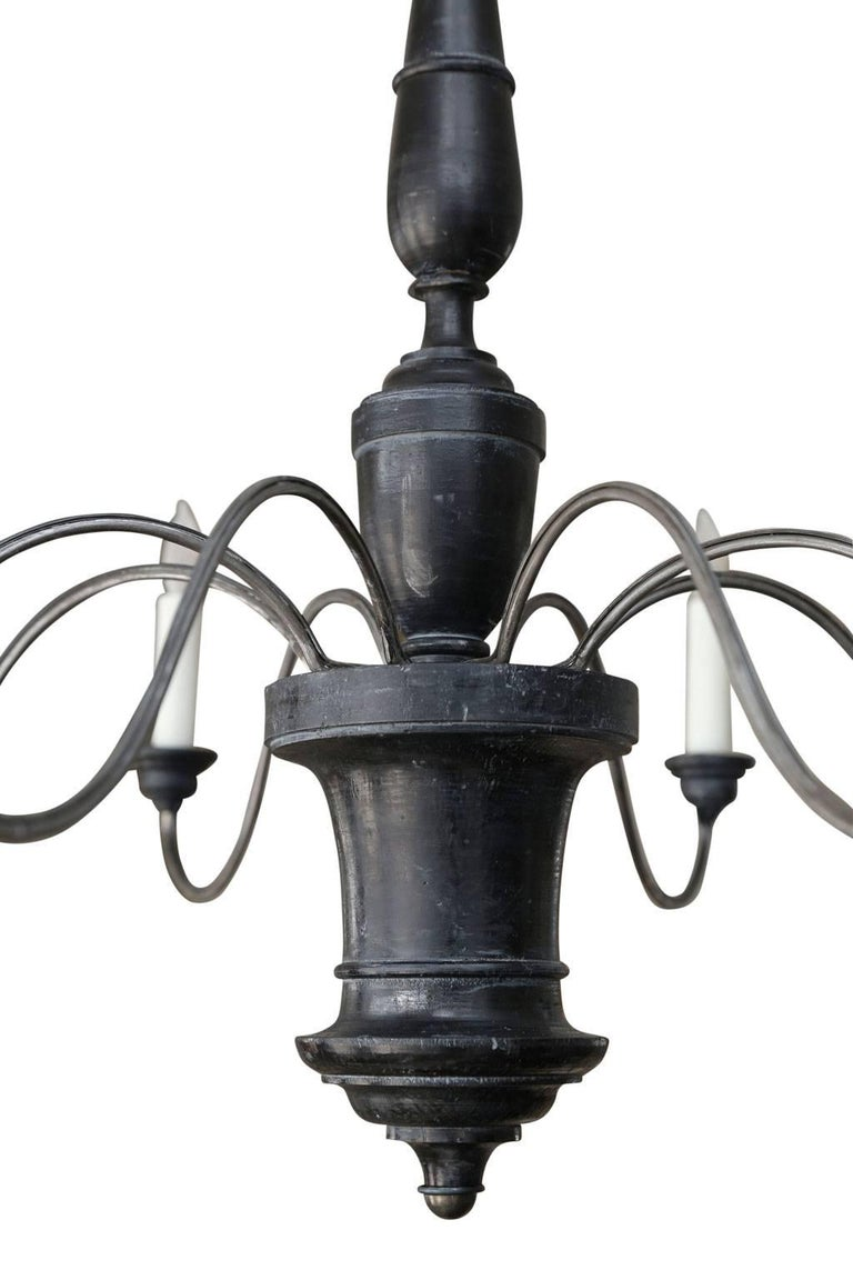 Ebonized wood and iron chandelier from Genoa, Italy. Chandelier consists of a turned wooden body (circa 1800-1820) in original ebonized finish, eight later undulating iron arms and wooden bobeche cups. Newly-wired for use within the USA using all UL