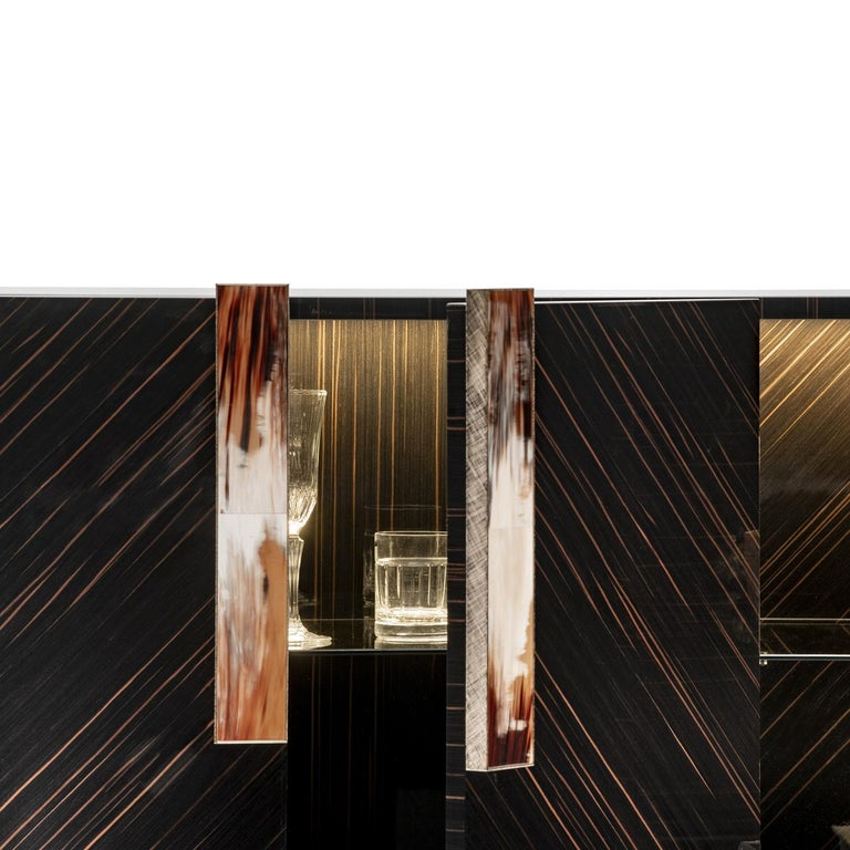 The lavish, glossy ebony veneer characterizing this 4-door, horizontal cabinet bestows it a luxurious allure. Its structure comprises a central compartment with a suggestive LED lighting system and the two side compartments boast plush, rectangular
