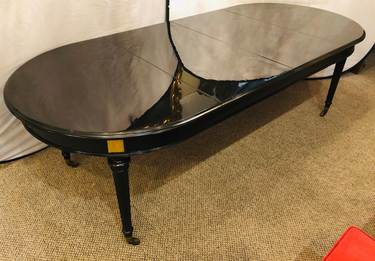A very fine ebony lacquered Hollywood Regency Louis XVI style crank two leaf dining table in the manner of Maison Jansen. Having recently been given a Steinway Grand black finish this wonderful Double 21 inch leaf dining table is certain to shine in