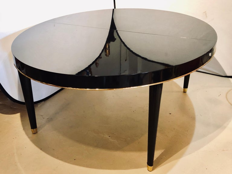 Ralph Lauren Paris one fifth dining room table with one leaf measuring 22 inches. this fully refinished dining table has an ebony lacquered finish the likes of the finest Steinway piano w outstanding gilt metal trim and sabots. The sleek and stylish