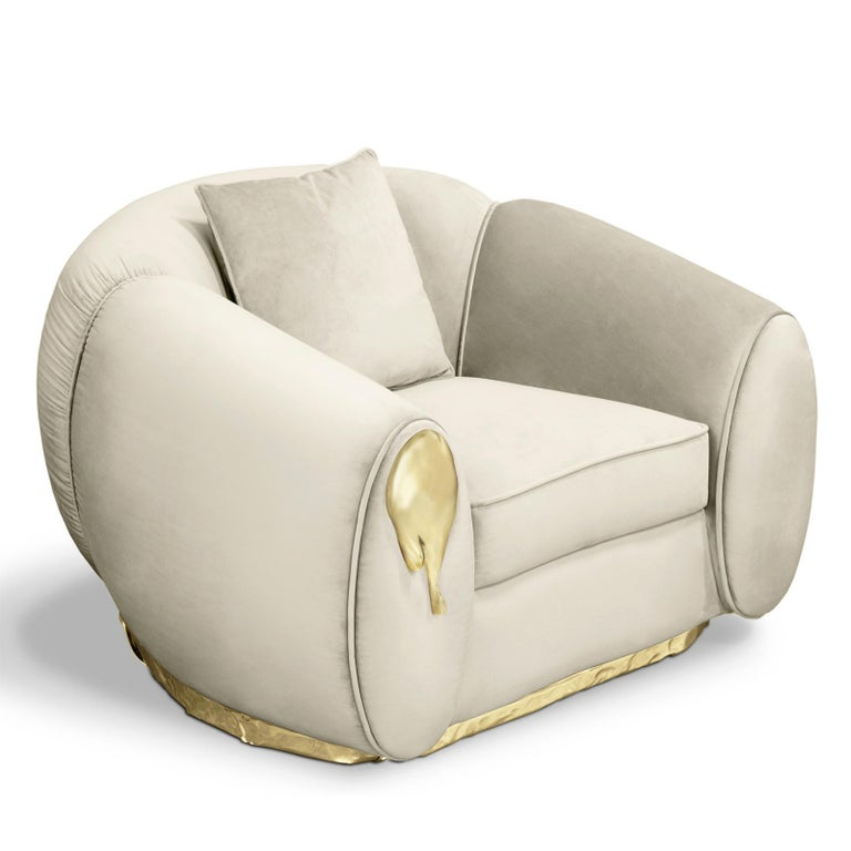 Armchair eclat with structure in solid wood and covered with cream grey genuine leather. Finishes with polished brass and with brass patina on base. Also available in sofa eclat.