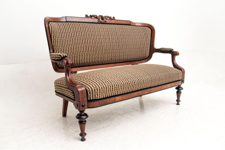 The antique sofa was made at the turn of the century in mahogany. Seat, backrest and partial armrests upholstered in fabric, stile subtly decorated with carvings. Very good condition, all supported on turned, stable legs. The restoration is
