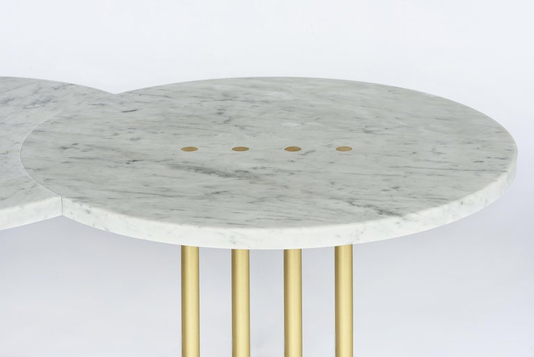 Two tables joined to form one, as when an eclipse universally unites two planets, struck by the excruciating light of the sun that forms small brushed brass dots.  The sun's rays support the table's structure. For a contemporary, minimal and