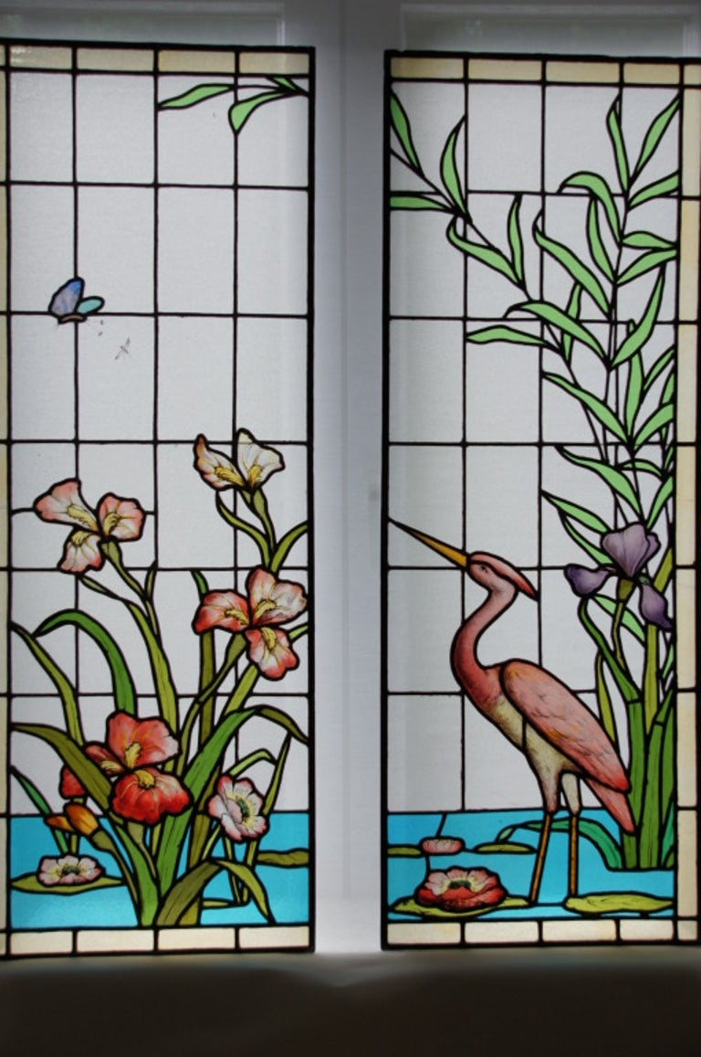 A beautiful and rare pair of stained and leaded glass window panels with heron, flowers and plants. Original 1900. Ecole de Nancy, France.