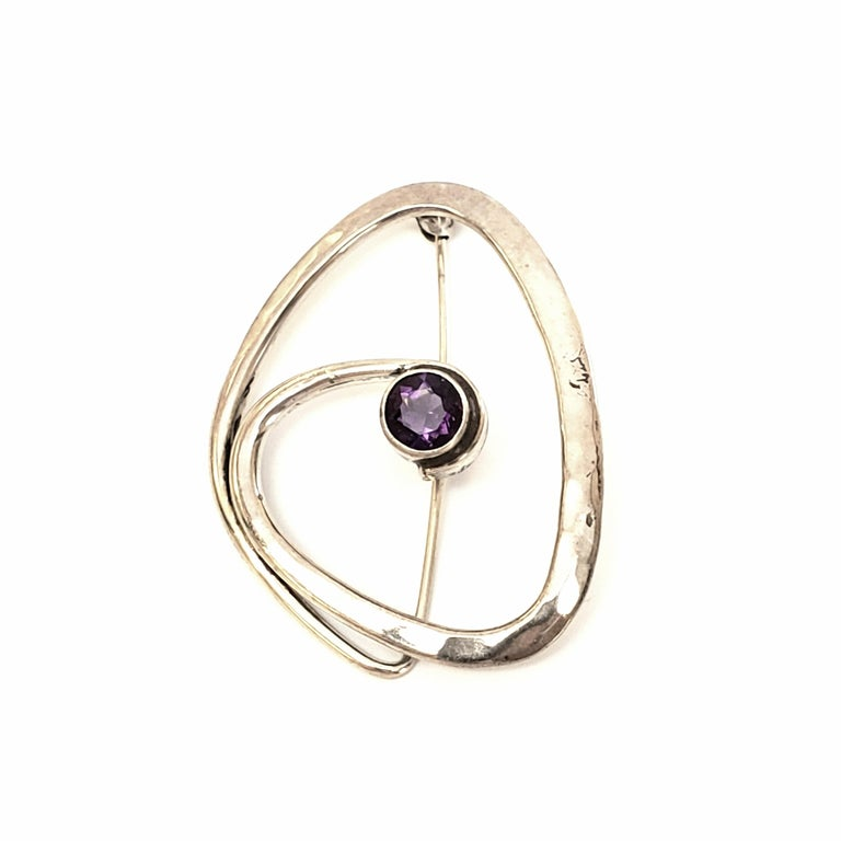 Sterling silver and amethyst pin designed by Ed Levin.  Highly sought after designer, Ed Levin, is known for making wearable art. This modernist design is slightly hammered and features a round, faceted, bezel set amethyst at its center.  Measures 1