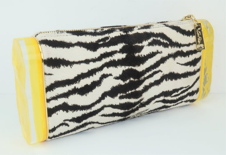 Edie Parker's designs by Brett Heyman are inspired by mid century fashions and each handbag is a unique and whimsical treasure.  This clever clutch is called the 'Lara' and features a zebra printed calf hair body accented by chunky acrylic pieces on