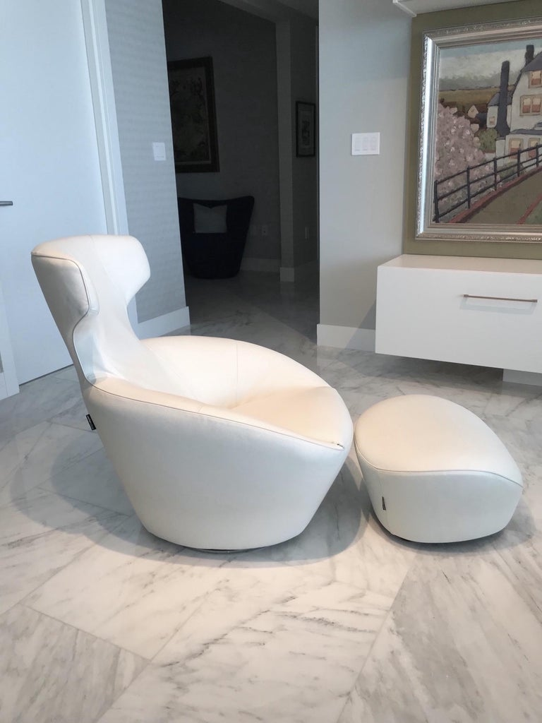 Ultra luxury lounge chair in custom ordered white leather, with matching ottoman. From the Edito series designed by Sacha Lakic for Roche Bobois. Chair has Mid-Century Modern inspired form reminiscent of Space Age designs. Features pivoting swivel