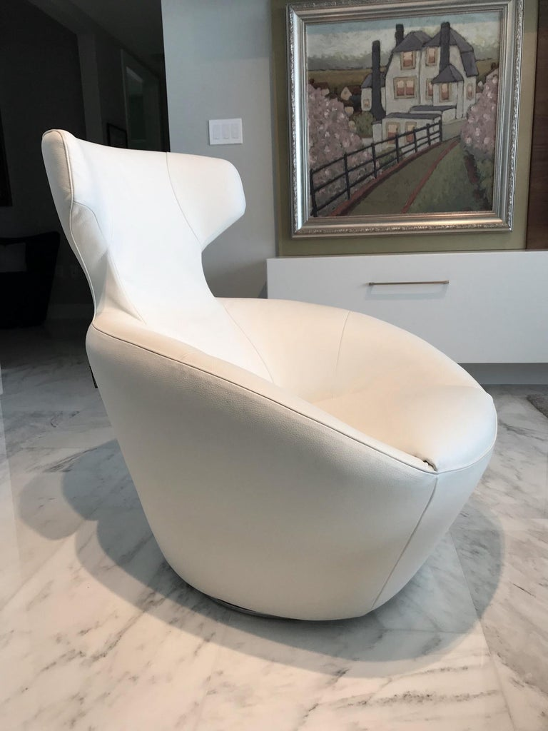 Ultra-luxury lounge chair in custom luxury white leather. From the Edito series designed by Sacha Lakic for Roche Bobois. Chair has Mid-Century Modern inspired form reminiscent of Space Age designs. Features pivoting swivel base design with auto