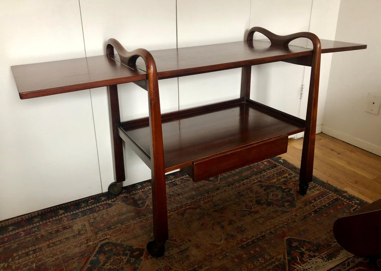Cuban mahogany rolling bar cart with inverse tapered legs, carved handles, one drawer, and two drop-leaf extensions. Designed by American designer Edmund J. Spence in a stylized Mexican Modern pastiche, and made in Mexico by Industria Meublera.