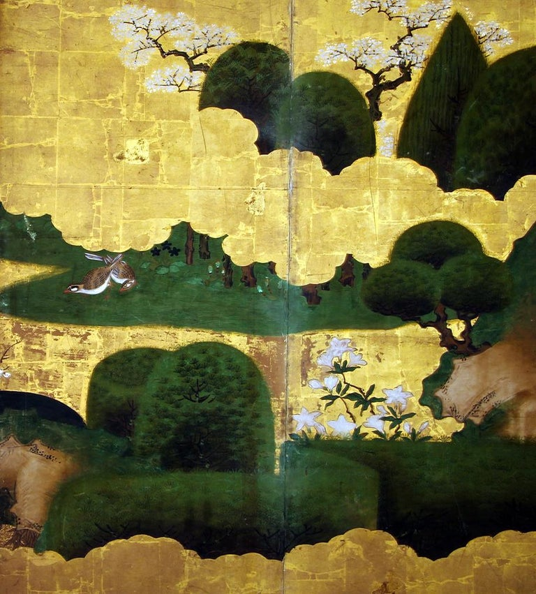 Edo six panel Japanese spring screen by Kano School, painted with mineral pigments on gold leaf and rice paper. The artist painted a pair of ducks in a lake with Sakura blossoms and pine varieties, a pleasant perspective between golden clouds.