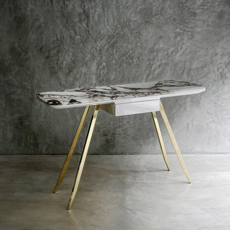 Available in two sizes, this elegant desk combines lightweight lines and perfectly balanced volumes. The stunning top with rounded edges fashioned of prized Breccia Medicea marble is attached to a further structural element in glossy,