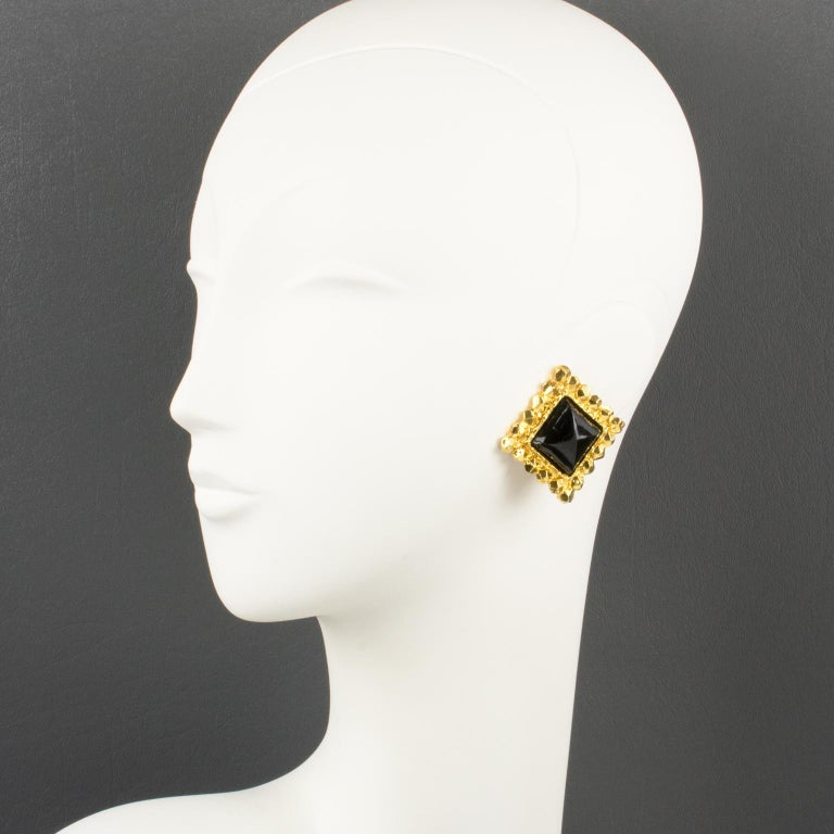 Lovely oversized Edouard Rambaud Paris signed clip-on earrings. Geometric dimensional design with a gilt metal square framing in shiny finish aspect topped with resin cabochon in licorice black color. Signed underside: