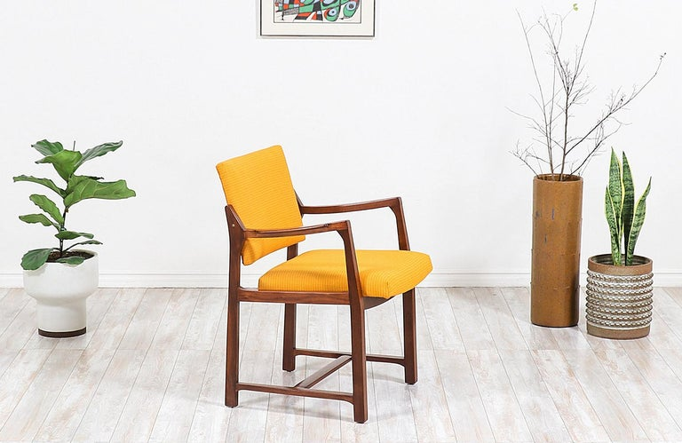Beautiful Mid-Century Modern armchair designed by American furniture designer, Edward J. Wormley, for Dunbar in the United States, circa 1950s. This sleek design features a solid walnut wood frame with soft curvilinear arms and a geometric base