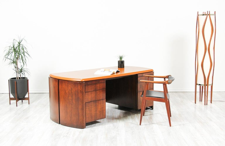 Beautiful and rare executive desk designed by Edward J. Wormley for Dunbar in the United States, circa 1950s. It features an elegant full-grain rust colored leather top on a walnut veneered hardwood frame. The front shows six drawers that vary in