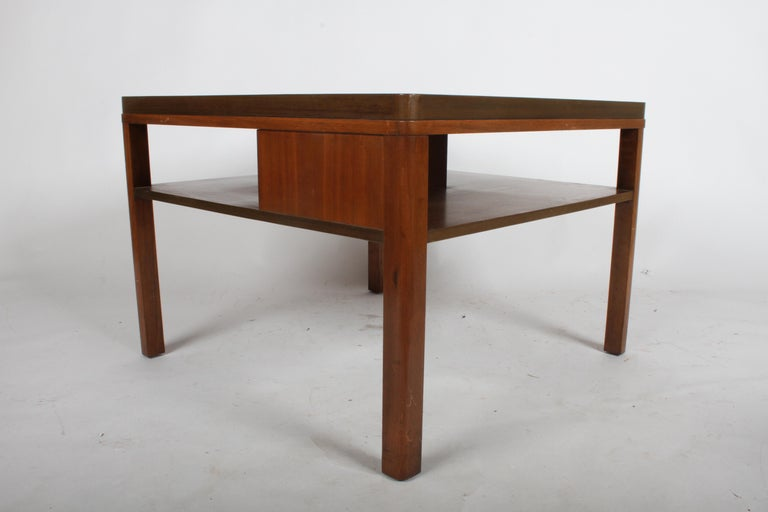 From the 1940s Dunbar Enduring Modern catalog is model # 2193, a single large end table with lower tier bookshelf by Edward J. Wormley. Rounded legs, has divider in center to hold books in place. Original Mahogany frame to be refinished prior to
