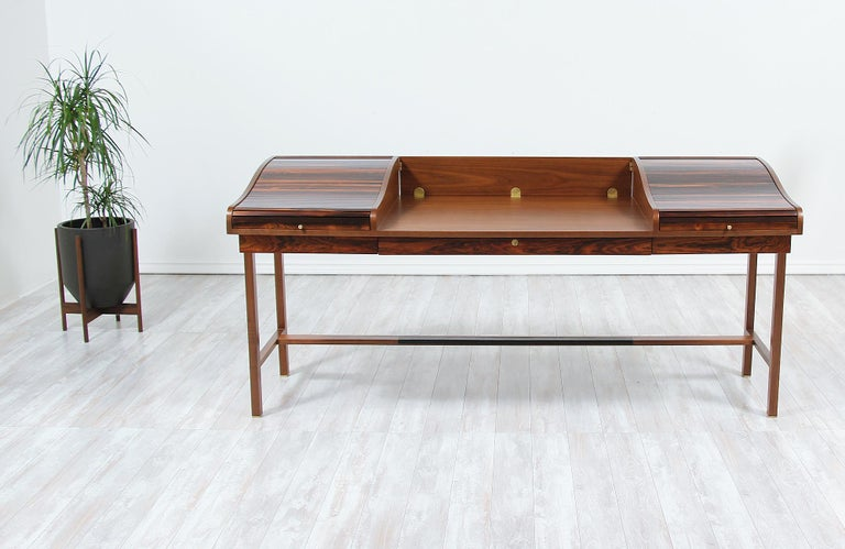 Elegant desk designed by Edward J. Wormley for Dunbar in the United States in 1957. This fabulous model #452 modern executive desk features a solid walnut wood frame and writing surface with a hinged panel at the back that drops, allowing it to