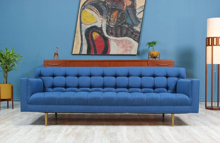 Mid Century Modern sofa designed by Edward J. Wormley for Dunbar in the United States circa 1950's. This sofa features a beautiful biscuit tufted detail on the blueberry tweed fabric upholstery which is complimented with the elegant solid brass