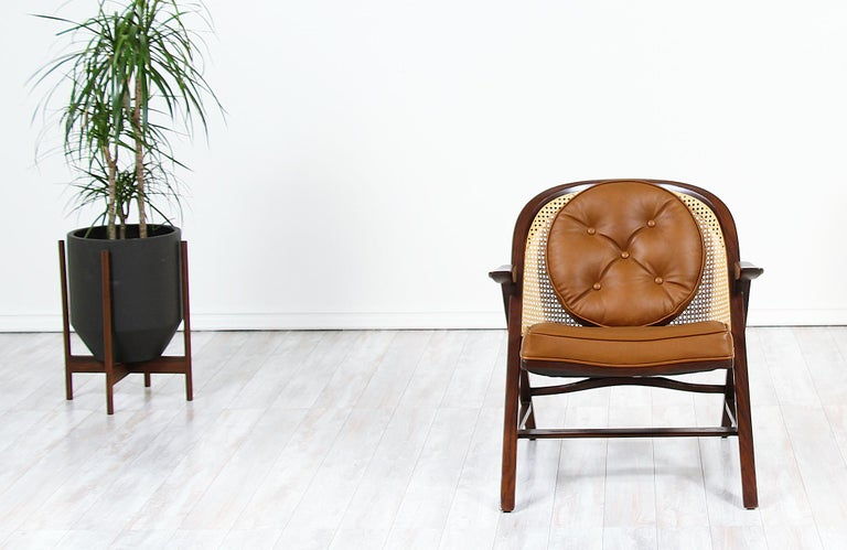 Iconic Model 5700-A lounge chair designed by Edward J. Wormley for Dunbar in the United States, circa 1950s. This rare design features a sturdily constructed walnut-stained oak wood frame with a newly woven cane backrest and new leather upholstery