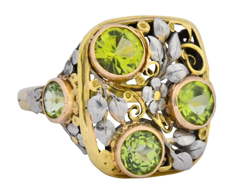 Yellow gold rectangular pierced design with white gold florals and foliate that continue onto shoulders  With five round cut peridot, bezel set in rose gold, weighing approximately 2.15 carats total, vibrant yellowish-green in color  Tested as 18