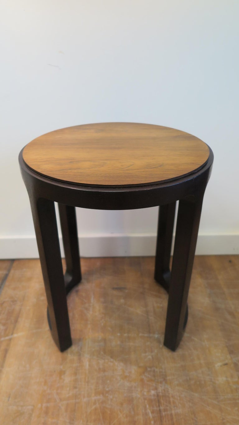 Dunbar round side table designed by Edward Wormely. Round walnut top on mahogany frame, having a natural color top with rich dark brown frame showcasing contrast in color and design. Original in very good condition with original badge and label. A